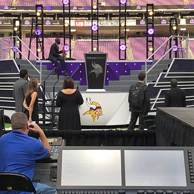 setting up a stage for a Minnesota Vikings event.